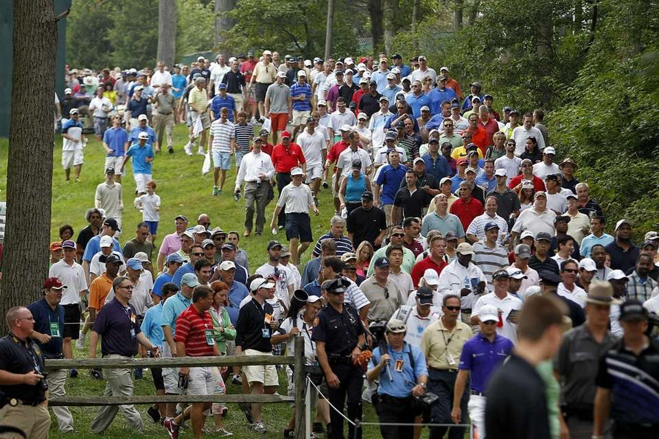 A large crowd follows Tiger Woods and Rory