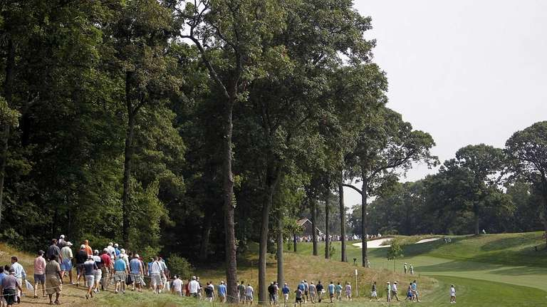 Crowds follow the paths along the second fairway