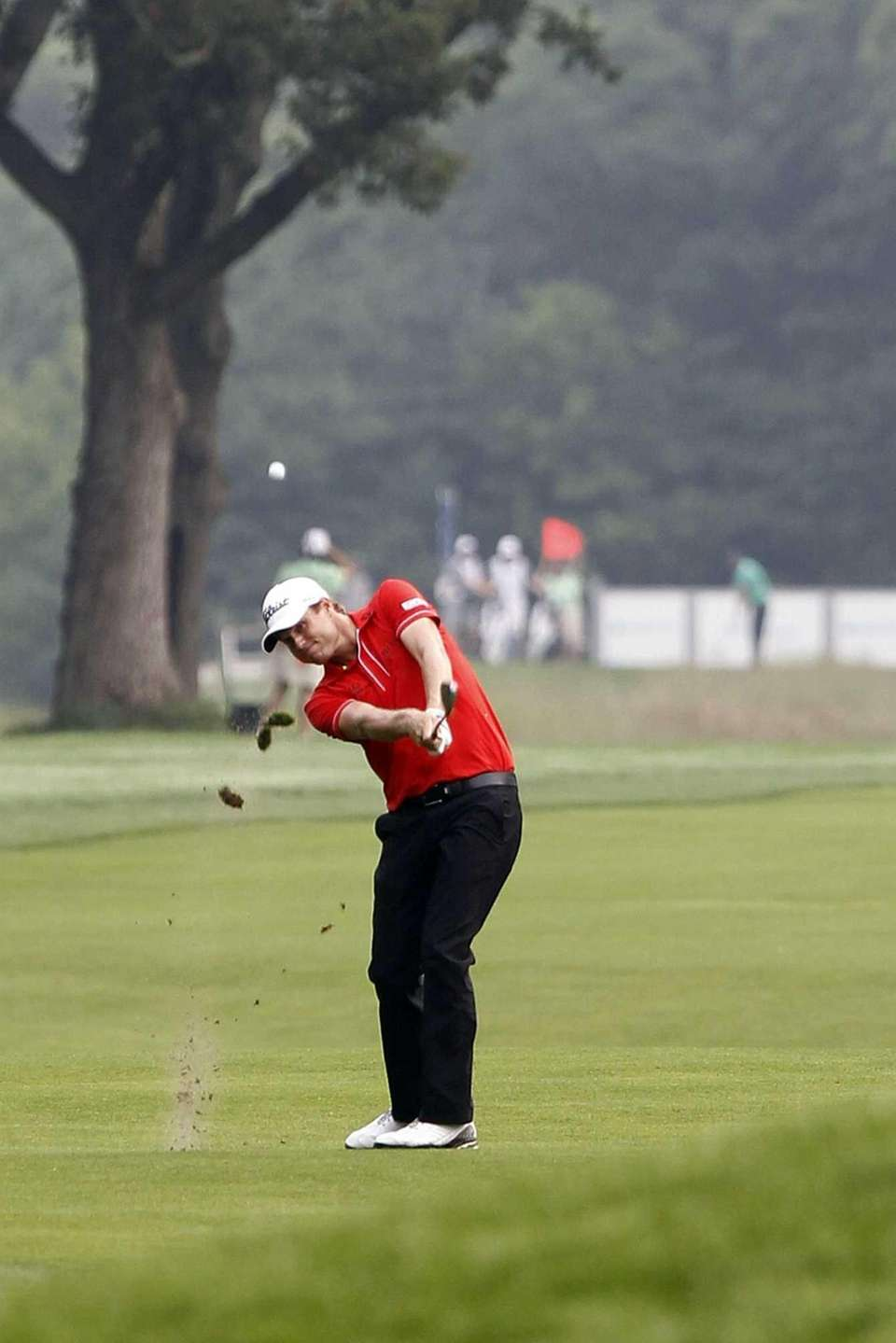Nick Watney hits a shot from the 13th
