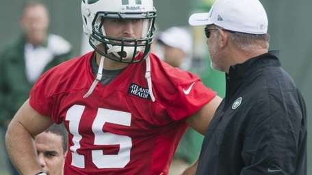 Tim Tebow talks with offensive coordinator Tony sparano