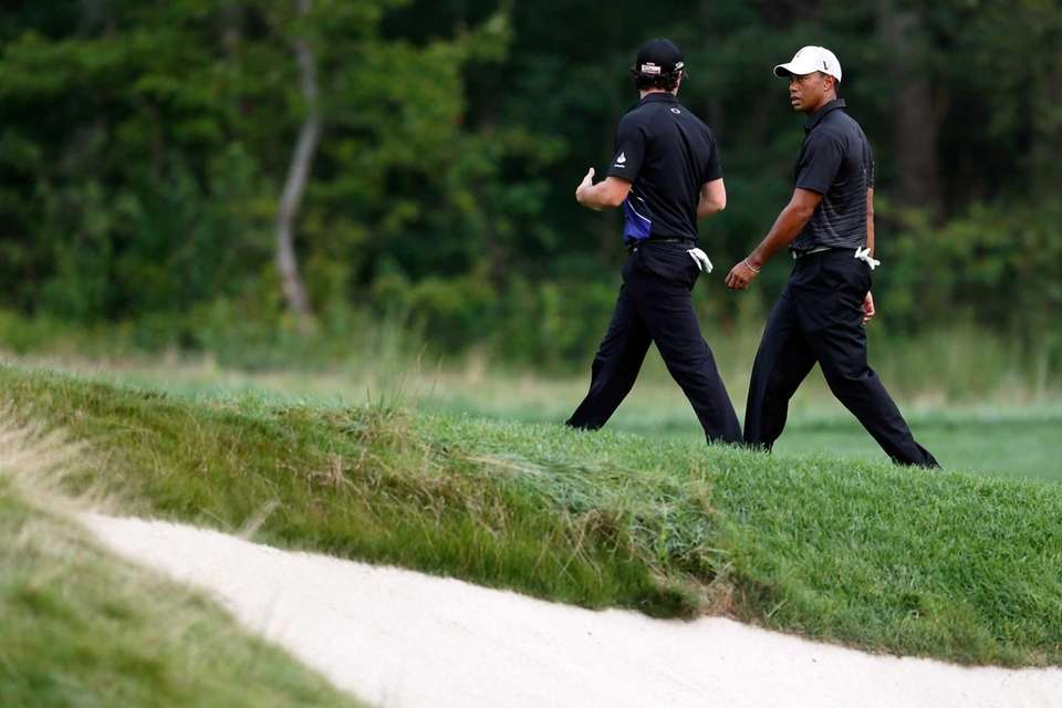 Tiger Woods (R) talks with Rory McIlroy of