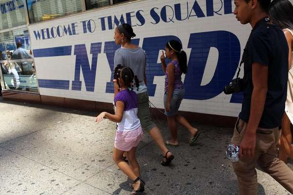 People walk by a Times Square police precinct