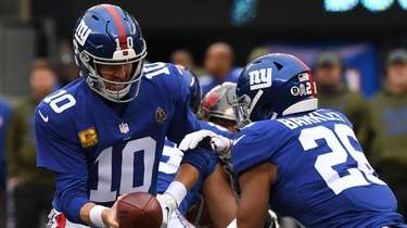 Giants quarterback Eli Manning hands the ball off
