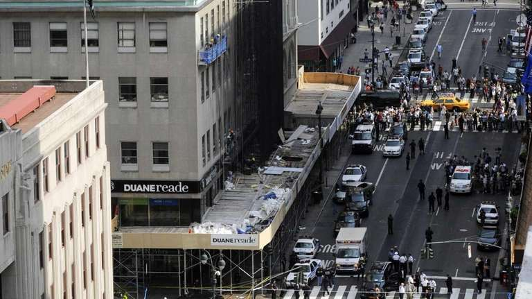 Police on a Fifth Avenue sidewalk investigate a