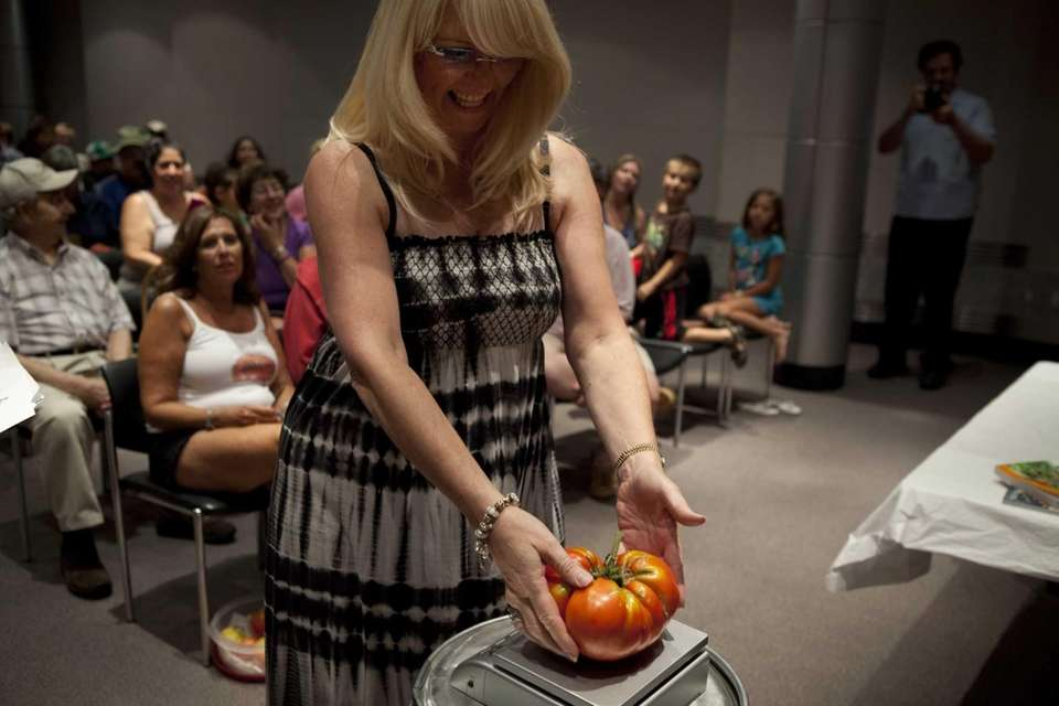 Ellen Papadopoulos gently places her 3rd-place-winning tomato on