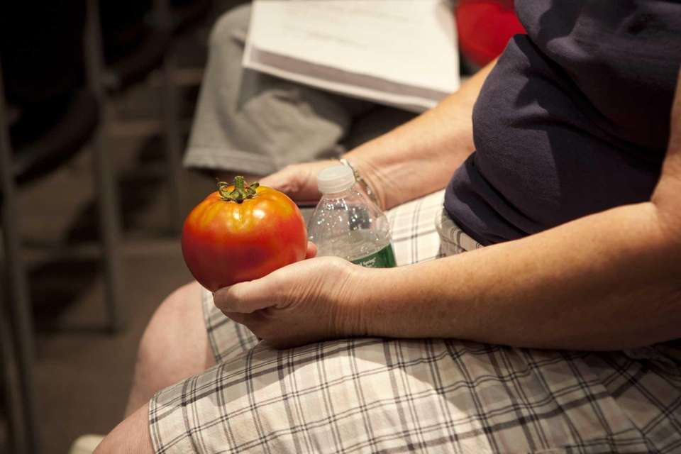A participant holds a tomato while watching the