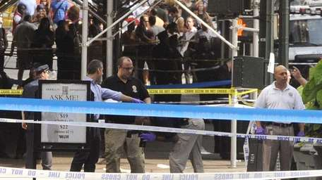 Police lean over a sheet covered body on
