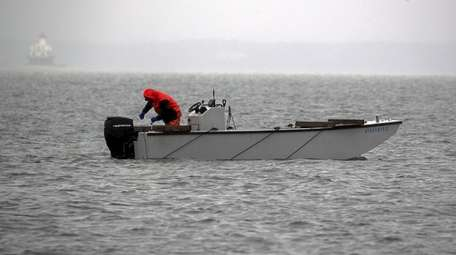 A bayman out scalloping on the bay during