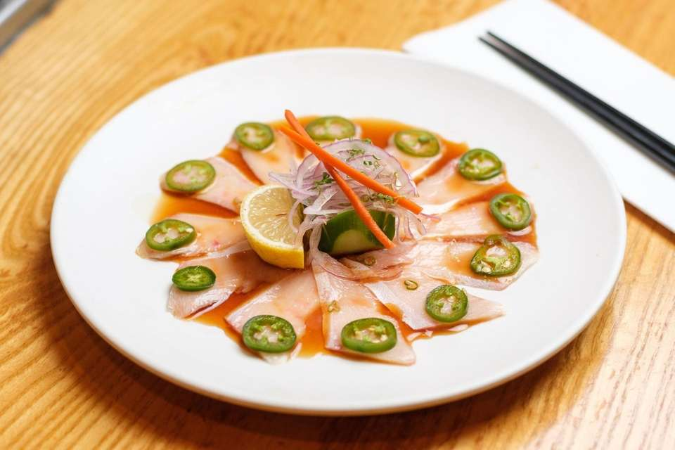 Yellowtail sashimi is served with soy sauce and