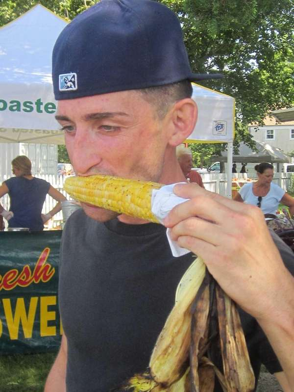 Michael Rowland, of West Sayville, enjoys roasted corn