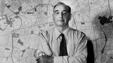 Robert Moses in front of a map of
