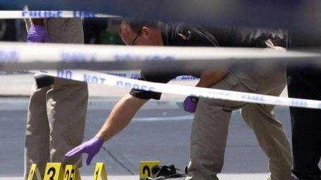 Investigators retrieve a black bag and gun after