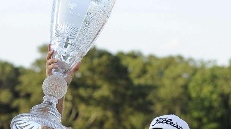 Nick Watney raises his trophy in the air