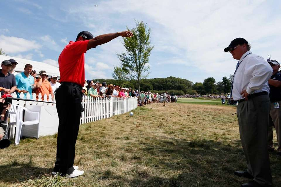 An official watches as Tiger Woods drops his
