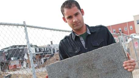 Robert Fleming, 31, stands with a concrete monument