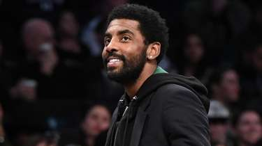 The Nets' Kyrie Irving looks on during a