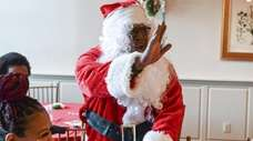 Santa greets children during a Christmas party at