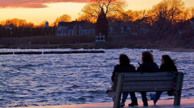 Three nature lovers watch the sunset at the