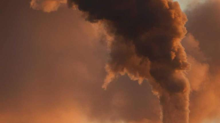 Geese flying past a smokestack at the Jeffery