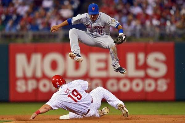 Ruben Tejada jumps over Laynce Nix of the