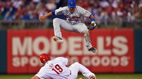 Ruben Tejada jumps over Laynce Nix of the