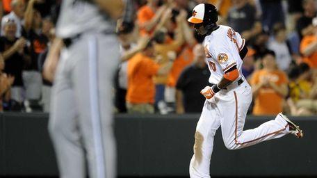 Baltimore's Adam Jones, right, rounds third base after