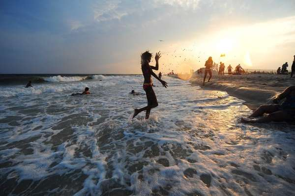 A girl chases the waves into shore at