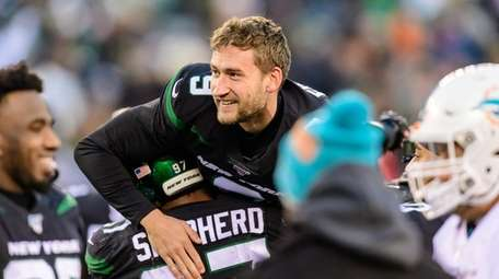 Jets kicker Sam Ficken is hoisted into the