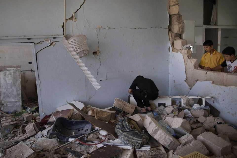 A Syrian man searches for belongings through the