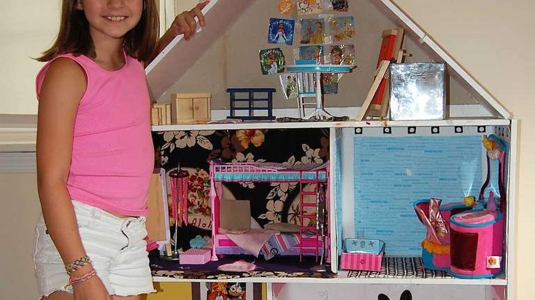Laura Jofre's daughter stands with her dollhouse, currently