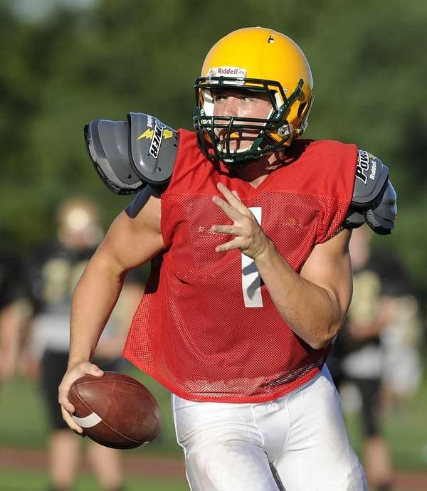 Ward Melville's quarterback runs with the ball against