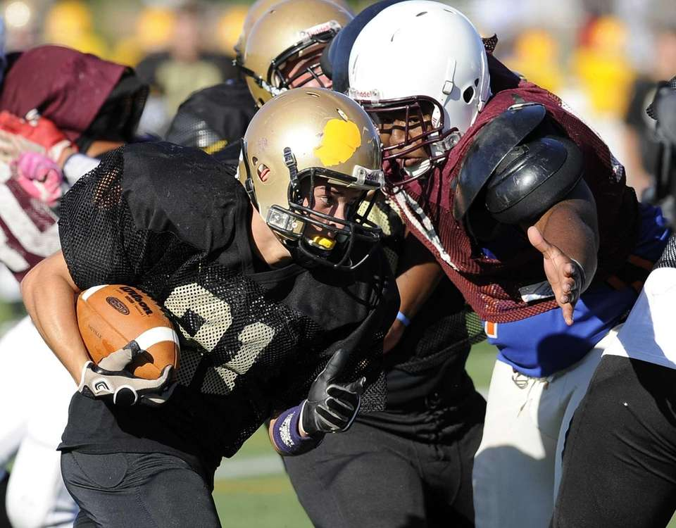 A Sayville receiver gains yardage against Bay Shore