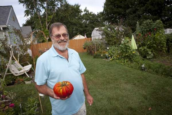 Gary Schaffe, in his Lindenhurst backyard garden, holds