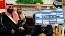 President Donald Trump shows a chart highlighting arms