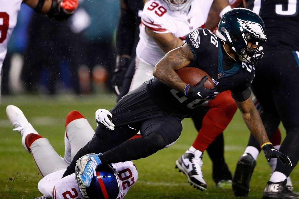 Philadelphia Eagles' Miles Sanders is tackled by the