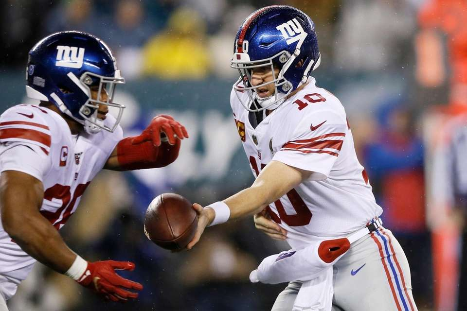 The Giants' Eli Manning, right, hands off to
