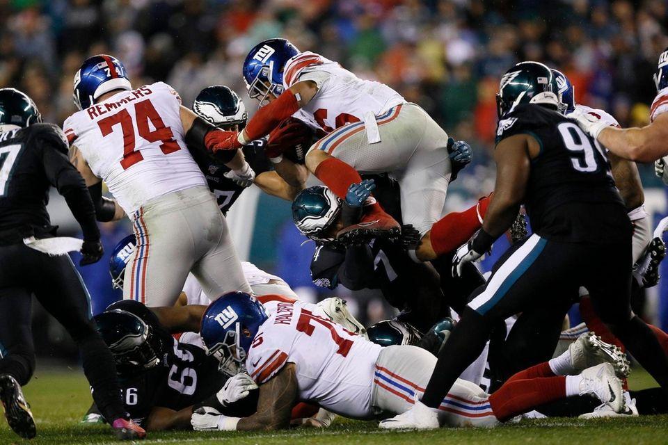 The Giants' Saquon Barkley leaps over Philadelphia Eagles'