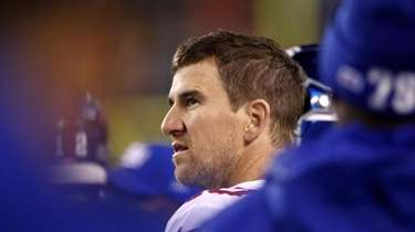 The Giants' Eli Manning looks on from the