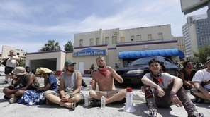 A few demonstrators sit on a Domino's Pizza
