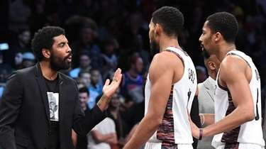 Brooklyn Nets' Kyrie Irving talks to guard Garrett