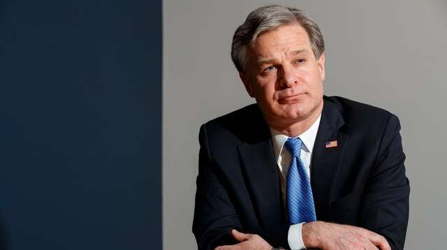 FBI Director Christopher Wray listens during an interview