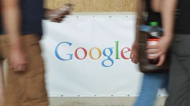 People walk past a Google stand at the