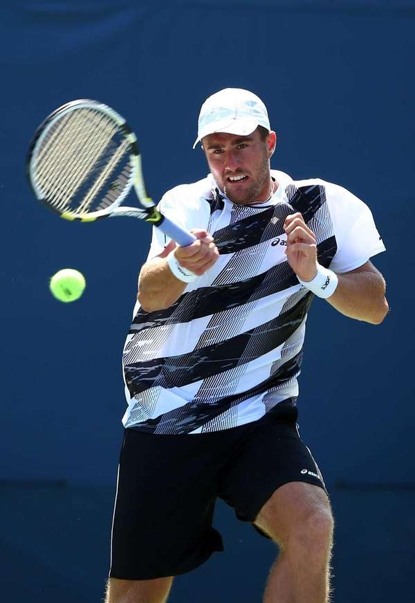 Steve Johnson returns a shot against Ernests Gulbis