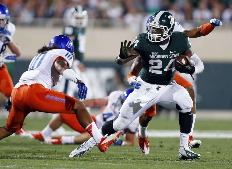 Michigan State's Le'Veon Bell, right, rushes against Boise