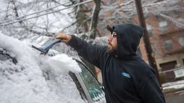 Mike Smith cleans off his SUV in Mineola