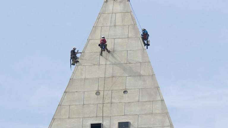 Workers rappel and inspect the top of the