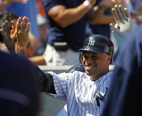 Robinson Cano is congratulated by teammates in the