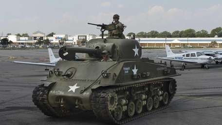 Steven DeMeo, lower front, drives a Sherman tank