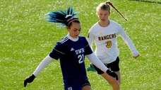 Shoreham-Wading River's Elizabeth Shields takes the ball past