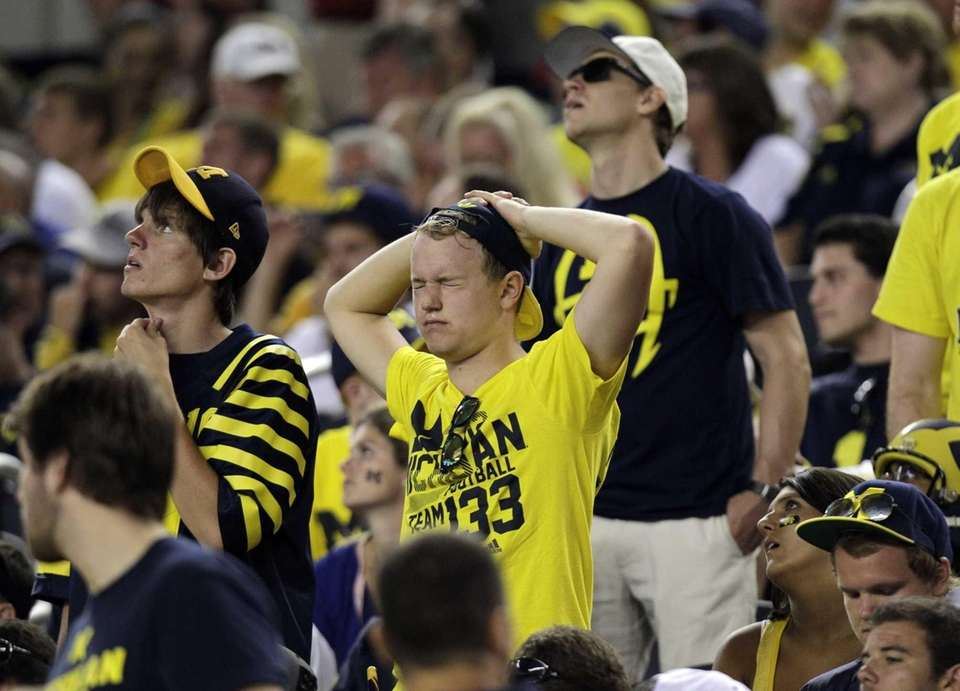 Michigan fans in the stands react to a